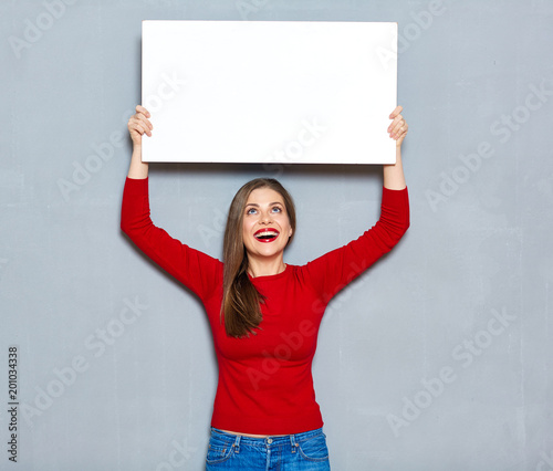 Foto Murales Young woman in red holding advertising billboard.