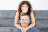 happy couple in home couch woman on sofa and man in floor - 201038991