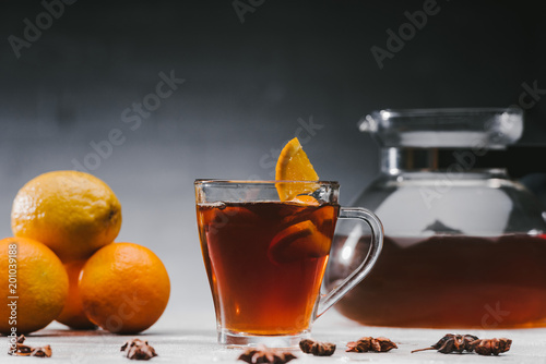 Gorąca czarna herbata w filiżance z cytrynami i pomarańczami
