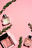 top view of bottles of perfumes with green branches on pink surface - 201039504