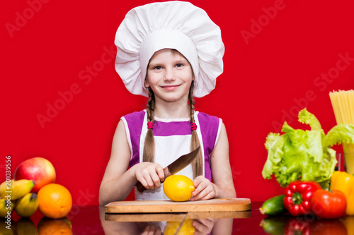 Happy little girl in chef uniform cuts fruit in kitchen. Kid chef. Cooking Process Concept