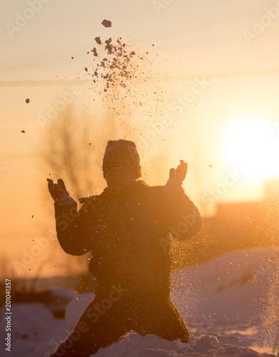 Chłopiec rzuca śnieg w niebo o zachodzie słońca