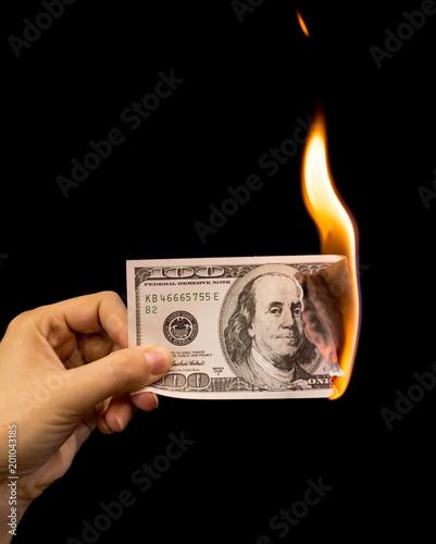 Sto dolarów palić w ręku na czarnym tle