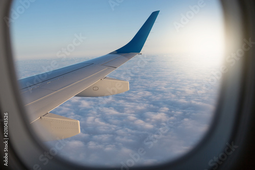 view through the airplane window, window frame, above the clouds, visible part of the wing and clouds, concept travel