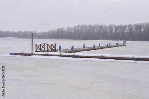 Foto op Plexiglas Kiev Winter scenery. Timber jetty in frozen river on a foggy winter day.