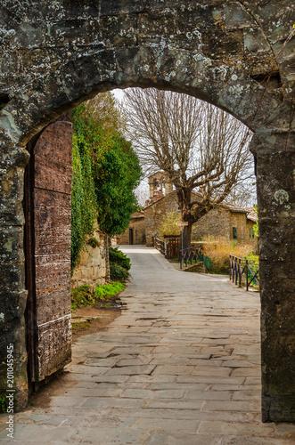 Fototapeta Cortona medieval historic center seen through Porta Montanina ancient gate, in Tuscany