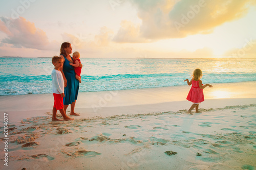 family on beach vacation- mother with kids at sunset sea