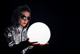 Portrait of young cosmic woman wearing in shiny hood and sunglasses holding the glowing sphere. Retro futurism concept.