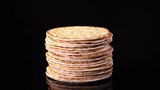 Traditional tasty flat bread (lavash, pita, chapati, scone) rotating against black background in 4K. Food texture with free space for text.  - 201057157