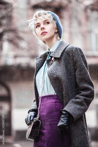 Plenerowy portret Yong dziewczyny piękny modny odprowadzenie w ulicie. Model ma na sobie stylowy pastelowy niebieski beret, bluzka, fiołkowa zamszowa spódnica, szary płaszcz, z małą srebrną torbą crossbody. Kobieca moda