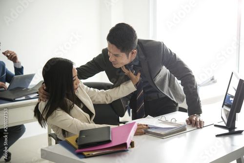 Foto Murales Businessman sexually harassing businesswoman colleague in office.