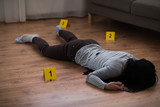 murder, kill and people concept - dead woman body in blood lying on floor and bullet sleeves at crime scene (staged photo) - 201077956