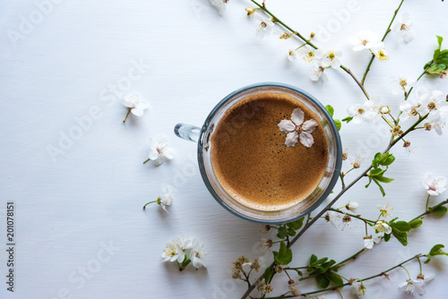 Fresh aromatic coffee and spring twigs on a white background.