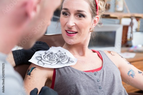 Portrait of a trendy woman sitting on the chair while getting a new cool tattoo in the professional studio of a creative artist
