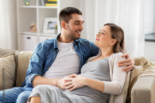 pregnancy and people concept - happy man hugging pregnant woman at home