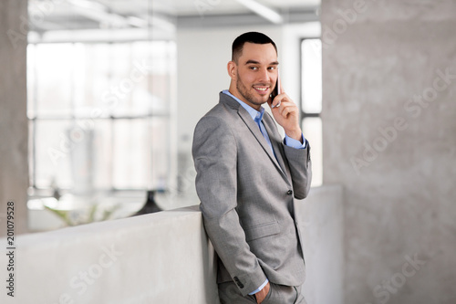 business people, technology and corporate concept - happy smiling businessman calling on smartphone at office
