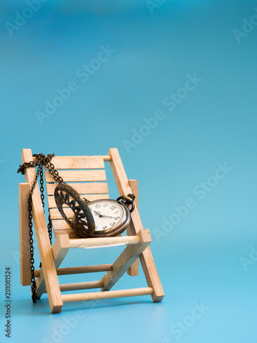 Pocket watch on the wooden beach chair on blue background (isolated). copy space for text and content. concept of vercation time and relax time.