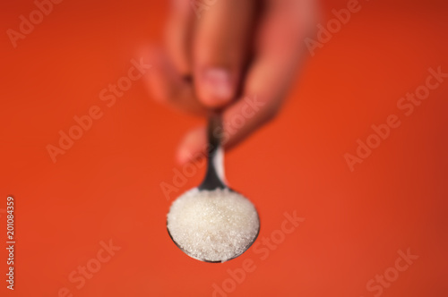 sugar in a spoon which is held by a hand on an orange red background