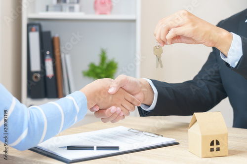 Woman say yes to sign loan contract for buying new home concept with key - hand shaking.