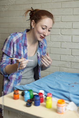 Foto Murales Photo of girl who drawing acrylic paints on blue clothes
