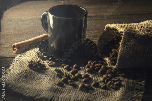 A cup of coffee and beans on an old kitchen table