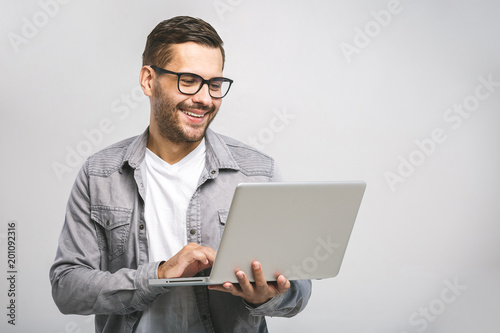 Fridge magnet Confident business expert. Confident young handsome man in shirt holding laptop and smiling while standing against white background