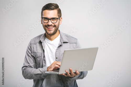 Confident business expert. Confident young handsome man in shirt holding laptop, looking at camera and smiling while standing against white background