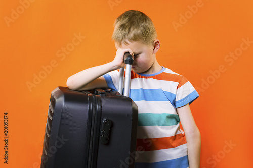 cute boy with a suitcase on a bright orange background