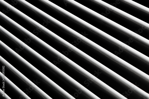 An abstract snapshot of a close-up illuminated grille that is angled with a dark background for patterns and backgrounds. - 201093382