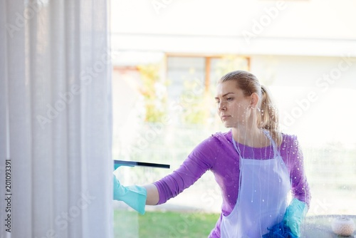 Foto Murales Young woman in white apron washing windows.