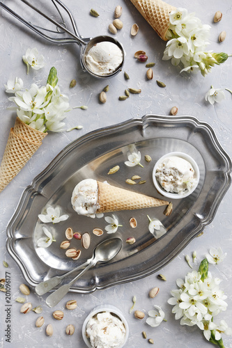 Foto Murales Close-up photo of fresh ice-cream on metal tray with white flowers and nuts