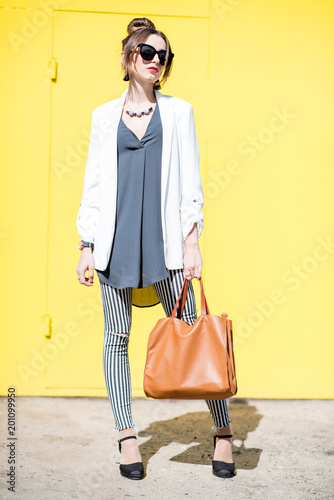 Business woman portrait on the yellow background outdoors