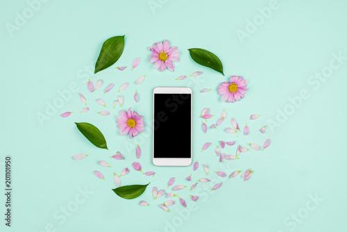 Biały smartphone z czarnym copyspace ekran z liśćmi, kwiaty pąki i płatki wokół.