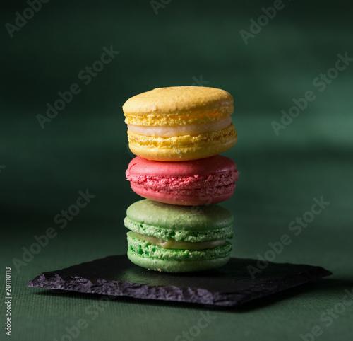 Foto Murales Assorted macarons on dark green background
