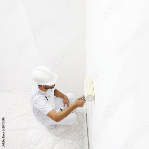 View from top painter man at work with a paint roller, wall painting concept