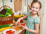 Child girl cooking in home kitchen, chopping tomatoes. Basket of vegetables and fresh fruits in kitchen interior. Healthy food concept