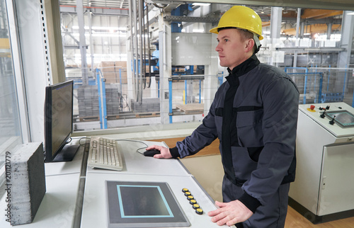 Engineer worker at control room. Portrait of a young technician worker in a factory. The operator monitors the work process from control room