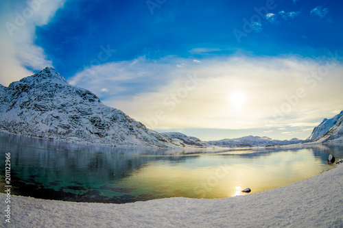 Foto Murales Gorgeous outdoor view of clear water in a lake with a sun reflecting, with a huge mountain covered with snow in Lofoten Islands