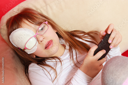 Toddler girl with bandage on eye playing games