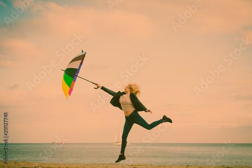 Kobiety doskakiwanie z kolorowym parasolem na plaży