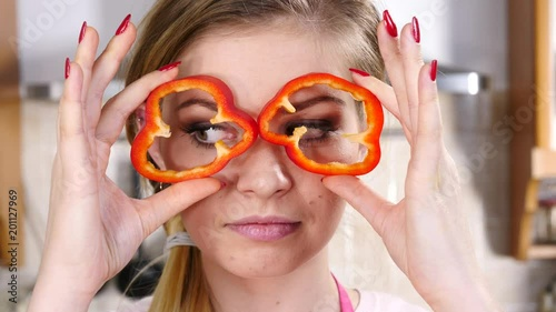 Funny playful woman having fun pretending red bell pepper rings are eyeglasses. Healthy food and dieting concept.