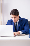 Young handsome businessman employee working in office at desk - 201131531