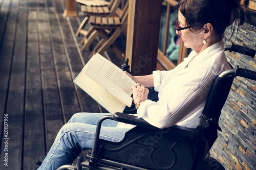 A woman sitting on a wheelchair and reading