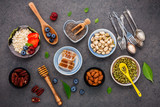 Ingredients for the healthy foods background Mixed nuts, honey, berries, fruits, blueberry, orange, almonds, oatmeal and chia seeds .The concept of healthy food set up on dark stone background. - 201146183
