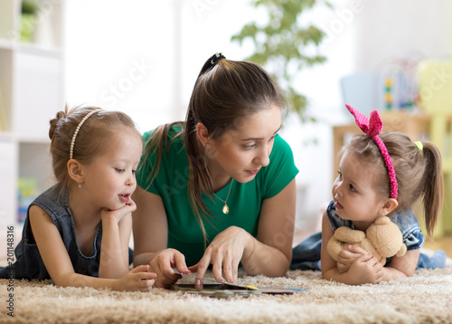 Foto Murales Young mother reading a book to her kids daughters. Children and mom lying on rug in cozy living room.
