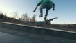 Skateboarder performs tricks on the ramp outdoors in sunset