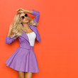 Beautiful Blond Woman In Violet Mini Skirt, Jacket And Sunglasses Is Posing With Arms Raised