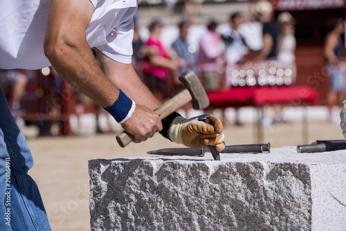 Close-up of the hands of a stonemason, hitting the stone