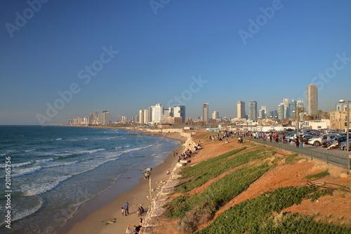 Tel Awiw, Izrael, widok na zatokę morza, nabrzeże z zielenią i umocnieniami, odpoczywających ludzi, ulicę z zaparkowanymi samochodami, w tle drapacze chmur, słonecznie
