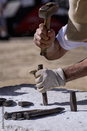 Close-up of the hands of a stonemason, hitting the stone - 201165902